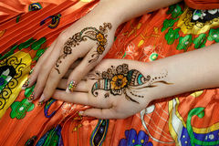 Two womans hands mehendi picture orange bright fabric with pleats. Indian picture on hands palms, mehendi tradition decoration, resistant design by special paint Stock Photo