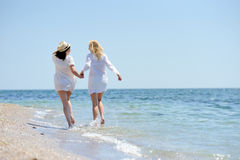 Two womans in white dress running on the beach Royalty Free Stock Photography