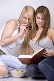 Two women. Two pretty womem on grey background eating chips Royalty Free Stock Photos