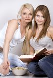 Two women. Two pretty womem on grey background eating chips and reading book Stock Image
