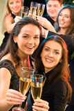 Two women. Portrait of young women raising up their bocals of champagne stock image