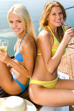 Two women. Portrait of two pretty women in swimwear drinking the cocktails Royalty Free Stock Photos