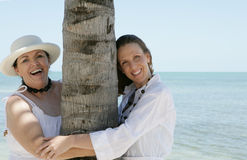 Two Women. Embracing a palm tree on their vacation Royalty Free Stock Images