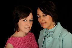 Two women. Close up of two women, one African American and the other caucasian.  One in hot pink and the other in turquoise.  Isolated against a black background Royalty Free Stock Images