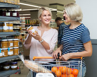 Two women of all ages are buying jam and honey royalty free stock photos