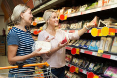 Two women of all ages are buying pcheese. Two women of all ages are buying cheese at the supermarket stock photos
