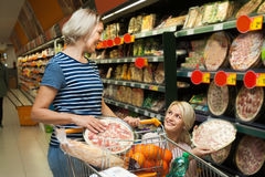 Two women of all ages are buying pizza at the supermarket royalty free stock photography
