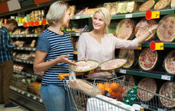 Two women of all ages are buying pizza at the supermarket. Two blonde smiling women of all ages are buying pizza at the supermarket royalty free stock photos