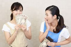 Women with money. Two women in apron with money Stock Images