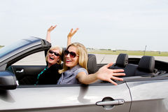 Two women with arms up in convertible Stock Images