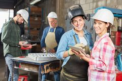 Two women as blue collar workers. Two women as apprentice of blue collar workers in metal construction lesson royalty free stock images