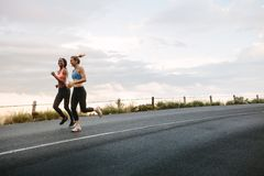 Two women athletes running. On road early in the morning with cloudy sky in the background. Fitness women jogging on road royalty free stock image