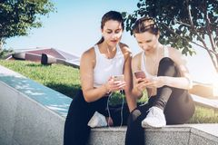 Two women athletes in sportswear sitting in park, relax after sports training, use smartphone, listening to music. royalty free stock images