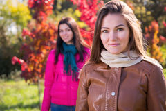 Two women in autumn park Stock Photos