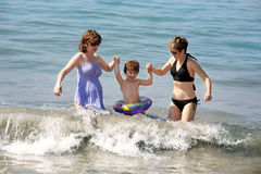 Two women and a baby. Playing in the ocean Stock Image