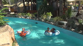 Two women and baby floating on swimming circles  on a slow river in garden. Two women and baby floating on swimming circles  on a slow river in tropical garden stock video footage