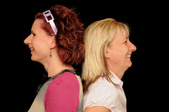 Two women back to back. Red-haired and blond women back-to-back, smiling, isolated on a black background, caucasian/white Stock Photos