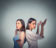 Two women back to back putting hands in air looking up in frustration Stock Image