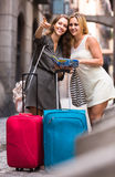 Two women with baggage checking route outdoors Stock Image