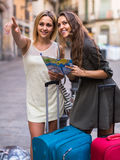 Two women with baggage checking route outdoors Stock Photography