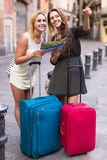 Two women with baggage checking route outdoors Stock Photo