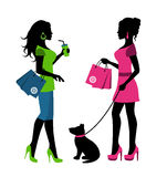 Two women with bags and a dog on a leash Stock Photos
