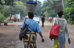 Two Women Balancing Baskets, in rural Zimbabwe, Africa. Two women carry loads on their heads, in a rural setting outside of Victoria Falls, zimbabwe Stock Photos
