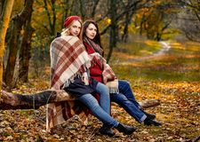 Two happy women basking. Two women basking with plaid in chill autumn park Stock Image