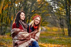 Two girlfriends basking. Two women basking with plaid in chill autumn park Royalty Free Stock Images