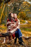 Two women basking. With plaid in chill autumn park Stock Images