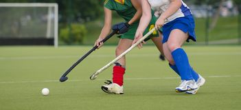 Two women battle for control of ball during field hockey game.  stock photos