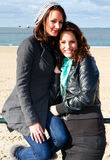 Two women on the beach. Two young women on the beach, posing in front of the sea on a beautiful autumn afternoon royalty free stock images