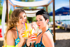 Two women in beach bar drinking cocktails Stock Image