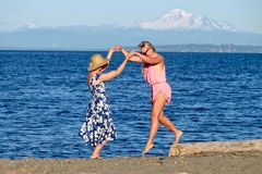 Two women on beach by blue ocean having fun. Royalty Free Stock Photography