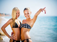 Two women on the beach showing the way stock images