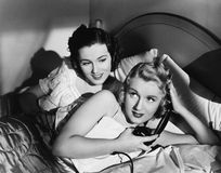 Two women in bed with telephone Stock Images