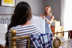 Two Women In Bedroom Choosing What To Wear Stock Photo