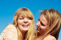 Two women best friends having fun outdoor. Two young women best friends blonde cheerful girls having fun outdoor against blue sky wind blowing in hair. Summer Royalty Free Stock Images