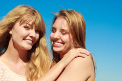 Two women best friends having fun outdoor. Two young women best friends blonde cheerful girls having fun outdoor against blue sky wind blowing in hair. Summer Stock Image