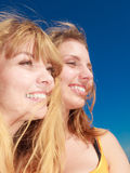 Two women best friends having fun outdoor. Two young women best friends blonde cheerful girls having fun outdoor against blue sky wind blowing in hair. Summer Stock Photography
