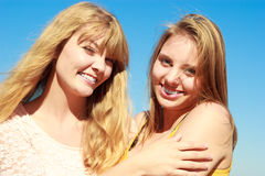 Two women best friends having fun outdoor. Two young women best friends blonde cheerful girls having fun outdoor against blue sky wind blowing in hair. Summer Royalty Free Stock Image