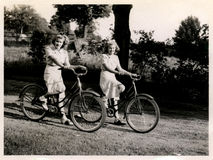 Two women on bicycles. Old silver print of two women (twins) on bicycles Stock Image