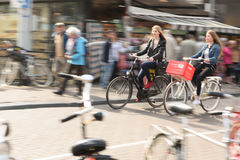 Two women bike to work in Amsterdam City Traffic. Royalty Free Stock Photography
