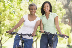 Two women on bikes outdoors smiling Stock Photo