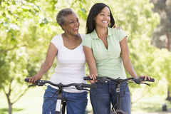 Two women on bikes outdoors smiling stock image
