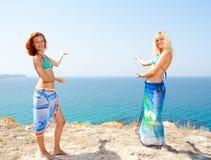 Two women in bikini inviting to sea. Two hot women in bikini and sarong inviting to sea Royalty Free Stock Photos