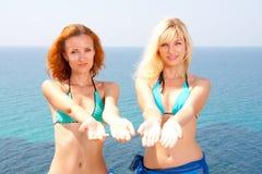 Two women in bikini inviting to sea. Two hot women in bikini and sarong inviting to sea Stock Photography