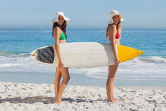 Two women in bikinis holding a surfboard Royalty Free Stock Image