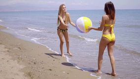 Two women in bikinis playing with a beach ball. Two pretty women in bikinis playing with a beach ball on a sandy tropical beach at the edge of the sea enjoying stock footage