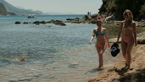 Two women in bikinis strolling on the public beach near the mountains. Attractive ladies slowly walk forward and communicate with each other at ease. They stock video